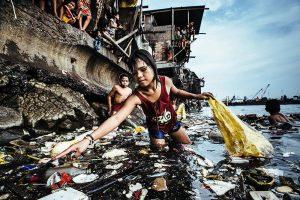 Kind sammelt Plastikmüll