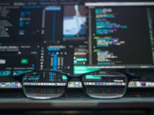 PC-Bildschirm mit Programmiercode und Brille