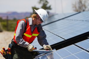 Mann arbeitet an einem Solarpanel