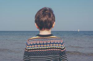 Kind mit dem Rücken zur Kamera vor dem Meer